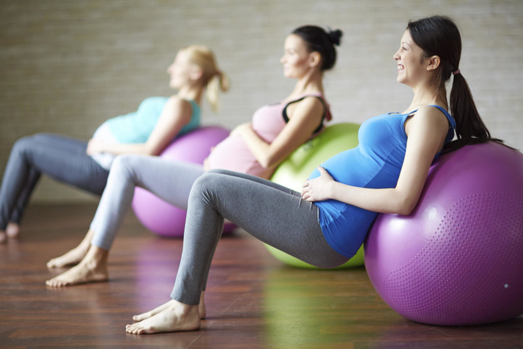 Several pregnant women exercising with ball in gym - Joy of Life Surrogacy