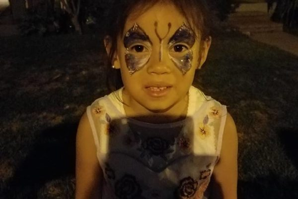 A little gril shown her face painting in front of her home - Joy of Life Surrogacy