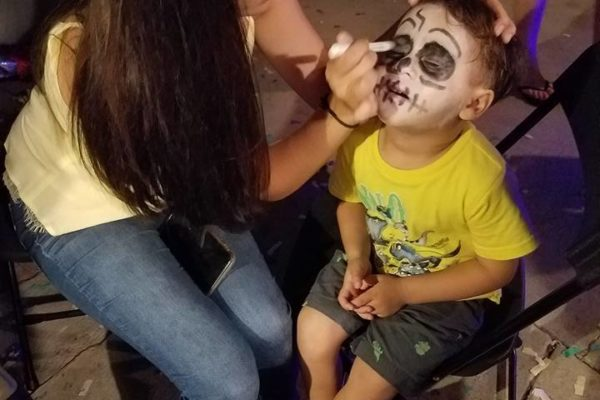 A kid getting face painting from Joy of Life employee - Joy of Life Surrogacy