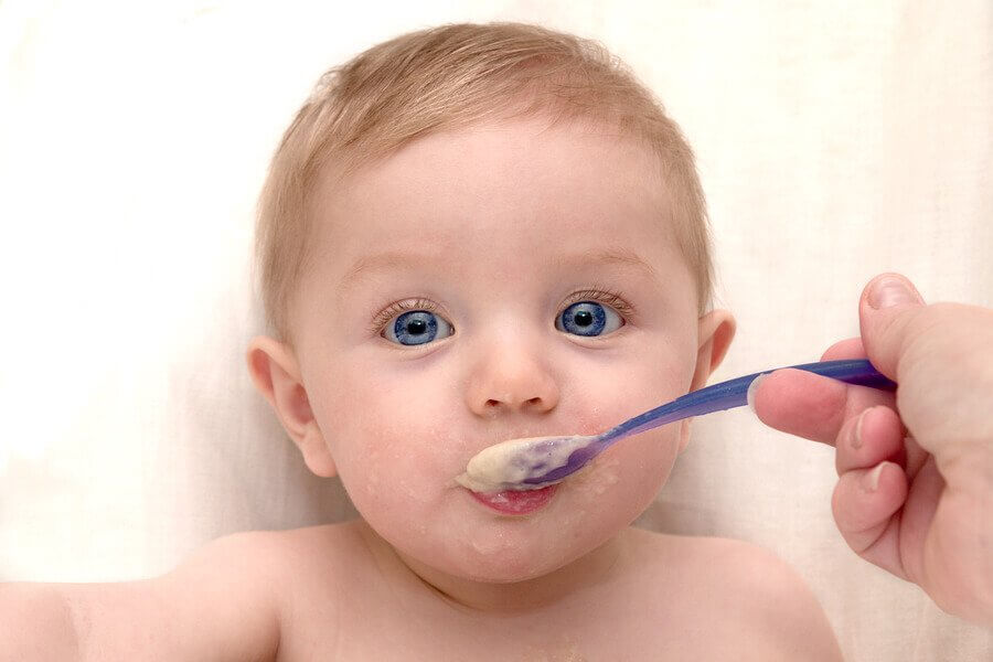 A blue-eyes newborn baby was eating his baby food - Joy of Life Surrogacy