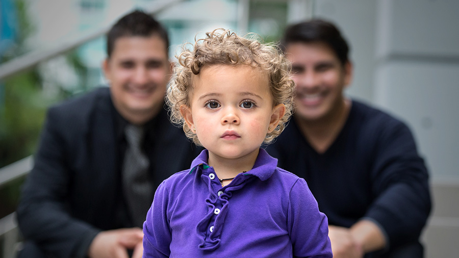 A little baby standing in front of his same-sex parents - Joy of Life Surrogacy